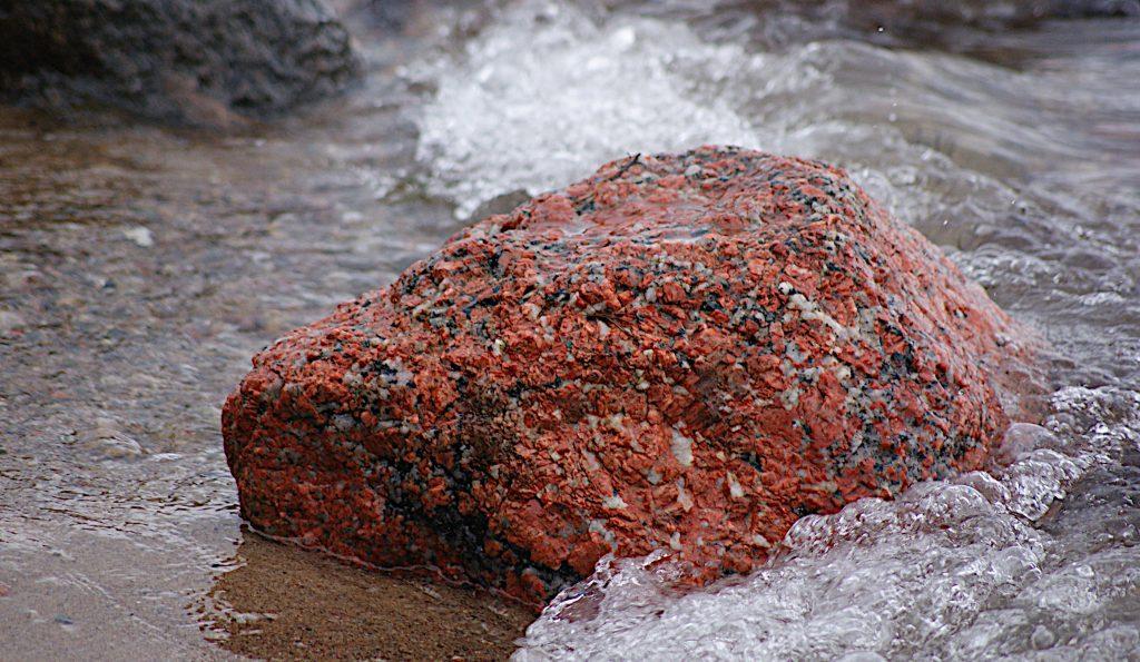Stein am Strand im Sand, in den Wellen